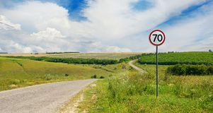 Road sign limiting speed on country road. Sunny day Stock Photos