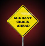 A road sign Migrant Crisis Ahead on ruby. A road sign Migrant Crisis Ahead on a ruby background stock photography