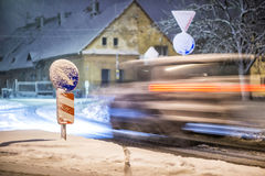 Road sign with moving car on the street after snowstorm, winter and night photography Stock Image