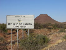 Road sign at Namibian border welcoming travelers to namibia with red mountain in backround. Roadside welcome sign royalty free stock photos