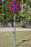 Road sign no parking under blue sky,on green gass. European Union. Stock Photo