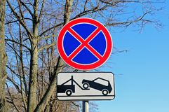 Road sign No stopping and parking. Also the plate about evacuation of incorrectly parked cars against trees and blue sky Royalty Free Stock Photo