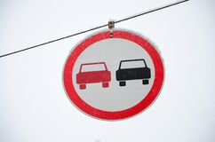 Road sign. Overtaking is prohibited. The sign prohibits overtaking all vehicles on the road section. A red and black car is depict. Ed in a framed red circle stock photos