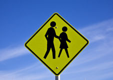Road sign people crossing. Road sign warns motorists that people may be crossing the road Stock Photo