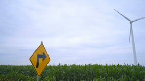 Road sign points to wind generator. Future of energy industry concept stock footage