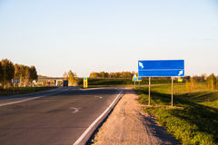 Road with sign pole and blue sky with clouds Royalty Free Stock Images