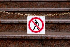 Road sign prohibiting the movement of pedestrians is hanging on a chain above the stairs stock photo