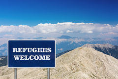 The road sign with Refugees welcome sign. On a background with mountains stock photos