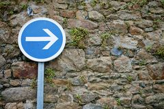 Road sign right arrow on the old stone wall background stock photography