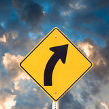 Road sign right curve. Road sign warning of dangerous curve with dramatic sky background Stock Image