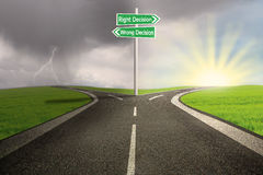 Road sign of right vs wrong decision. Green road sign of right vs wrong decision on highway with thunder storm background Stock Photo