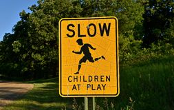 Sign Children at play. Road sign on a rural gravel road warning to `Drive Slow-Children at Play Stock Image