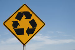 The Road Sign Series. Recycling symbol on a road sign against a blue sky background Royalty Free Stock Image