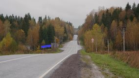 Road sign of settlement and retiring car on the autumn country road. Road sign of settlement and leaving car on an autumn suburban road stock video