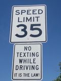 A road sign showing an instruction stating no texting while driving. A road sign showing a speed limit and also an instruction stating no texting while driving stock photos