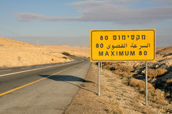 Road sign for speed limit (80). Warning sign or road sign for the maximum speed limit next to an empty road in Israel Royalty Free Stock Photos