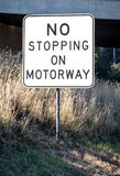 Road Sign Stating NO STOPPING ON MOTORWAY in Long Grass Stock Photo
