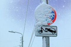 Road sign a stop is forbidden and the tow truck is carried by snow on a sky background.  Stock Image