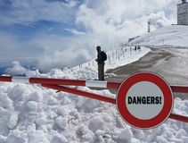 Road sign Stop. Warning of danger in the mountains. Avalanche retreat. Danger on the snow-capped mountain tops among the clouds. royalty free stock image