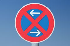 Road sign stopping restriction. European road sign on blue sky - stopping restriction. No standing at any time Royalty Free Stock Photos