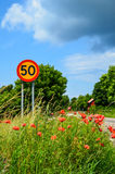 Road sign at summer flowers Stock Images