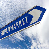Road sign to supermarket - sky & clouds. Road sign pointing to supermarket shown against dramatic sky with clouds Royalty Free Stock Image