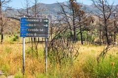 Road sign to villages: Apolakkia, Arnitha, Genandi, Vati, burnt after bushfire Rhodes, Greece royalty free stock photo