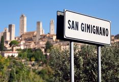 Road sign of town San Gimignano and ancient Tuscan cityscape on background. UNESCO World Heritage Site. Road sign of town San Gimignano and ancient Tuscan stock photos