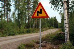 Road Sign. Traffic sign by a Finnish gravel road. Warning a curve ahead royalty free stock image