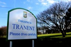Road sign for Tranent, East Lothian. An early morning shot of the street sign for Tranent in East Lothian with the light hitting the trees in the background royalty free stock photography