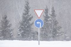Road sign turn left on a snowy road. Close-up. Background with trees with snow. royalty free stock photo