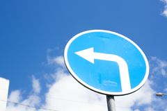 road sign turn on blue sky background, direction concept stock photo