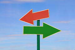 Road sign with two different arrows over blue sky. Road signpost with two blank copy space arrows, green and red, directing to different directions, left and royalty free stock images