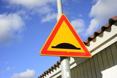 Road sign uneven road. Against the sky Stock Image