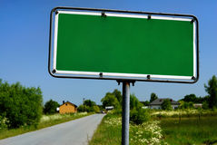Road sign with village in background Royalty Free Stock Images