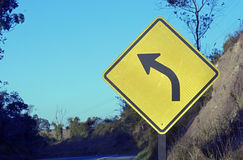 Road sign warning about left curve Stock Images