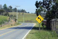 Road sign warning about left curve Stock Photos
