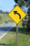 Road sign warning about left curve Stock Photo