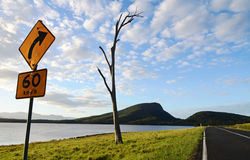 Road sign warning people of bendy roads ahead Stock Photography