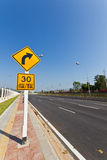 Traffic Signs. Road Sign warns Drivers to Limit Speed Ahead Dangerous Curve stock photography