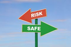 Road sign with two different arrows over blue sky. Road signpost with two arrows, green and red, with risk and safe words, directing to different directions Stock Image