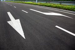 Road signs arrows on asphalted surface Royalty Free Stock Images