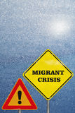 A road signs Attention and Migrant Crisis on blue Royalty Free Stock Photo