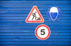 Road signs against a blue metal fence royalty free stock images