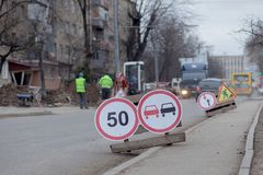 Road signs, detour, road repair on street background, truck and excavator digging hole.  royalty free stock image