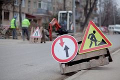 Road signs, detour, road repair on street background, truck and excavator digging hole.  royalty free stock photos