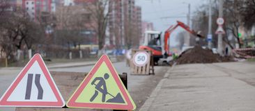 Road signs, detour, road repair on street background, truck and excavator digging hole.  royalty free stock images