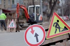 Road signs, detour, road repair on street background, truck and excavator digging hole.  royalty free stock photo