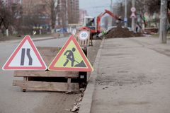 Road signs, detour, road repair on street background, truck and excavator digging hole.  royalty free stock photography