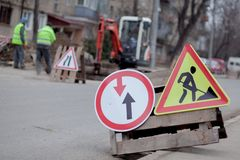 Road signs, detour, road repair on street background, truck and excavator digging hole.  stock photos